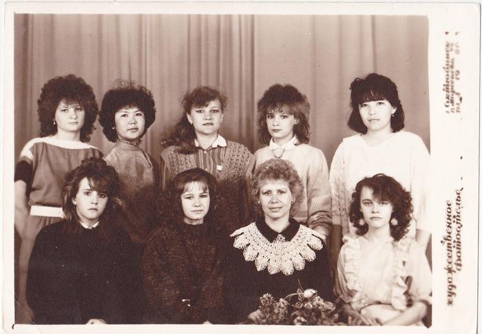 Фото. Наш кружок вязания. Девочка в платье с рюшами и с серёжками-ёжиками по левую руку от Любовь Ивановны - я. Мне там 16 лет.