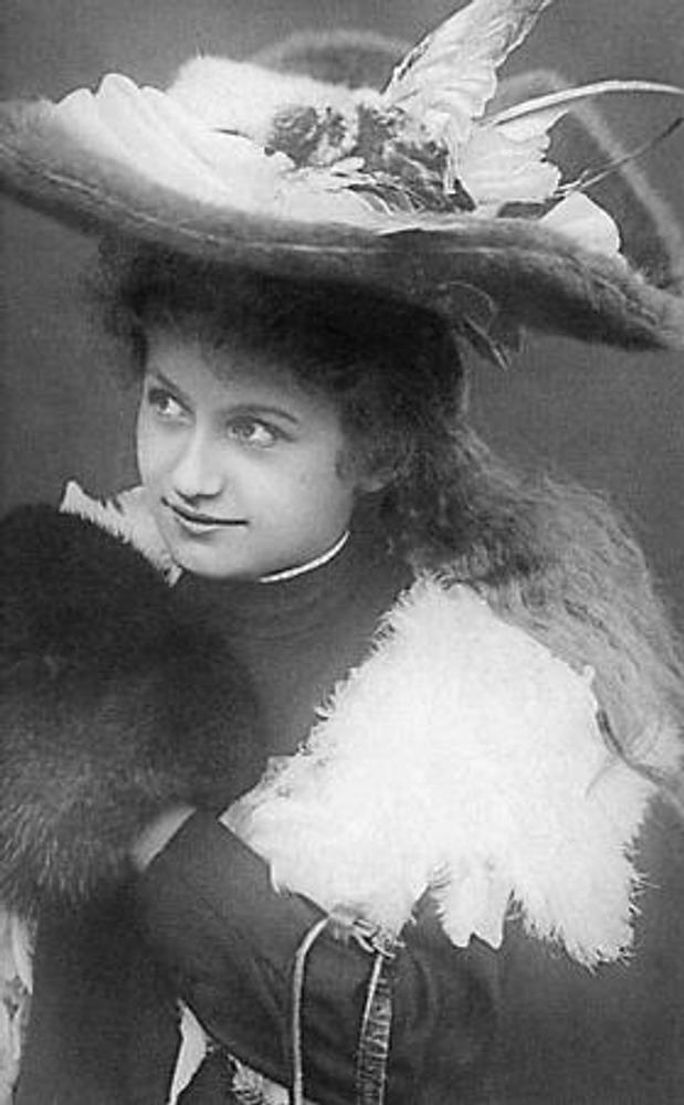 Конец 1900-х гг. Девушка в зимнем туалете, с собольей муфтой и в широкой фетровой шляпе, отделанной шелком и крыльями птицы, на плечах - горжетка из гагачьего пера.