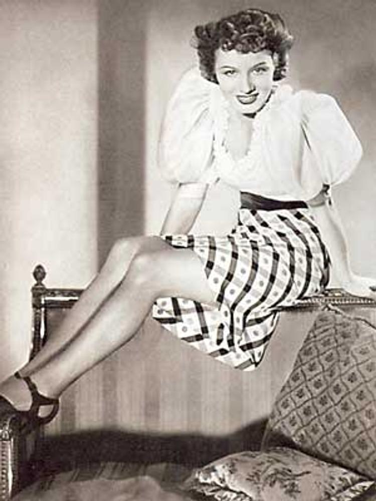 Фото. Актриса немецкого кино Мади Раль в белой блузке с пышными рукавами в баварском стиле и в клетчатой укороченной юбке. Мюнхен, 1941 г.