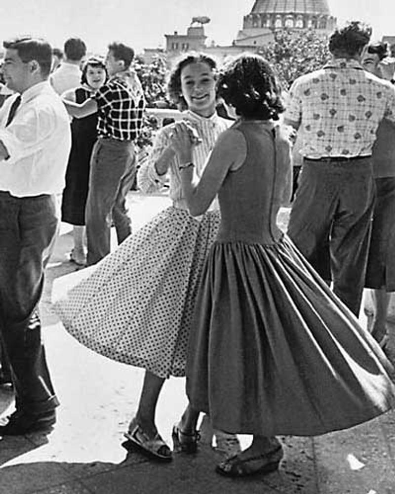 Фото. На Всемирном фестивале молодежи и студентов. Девушки одеты в широкие юбки стиля Нью Лук, мужчины в цветных рубашках. Москва, ВДНХ, 1957 г.