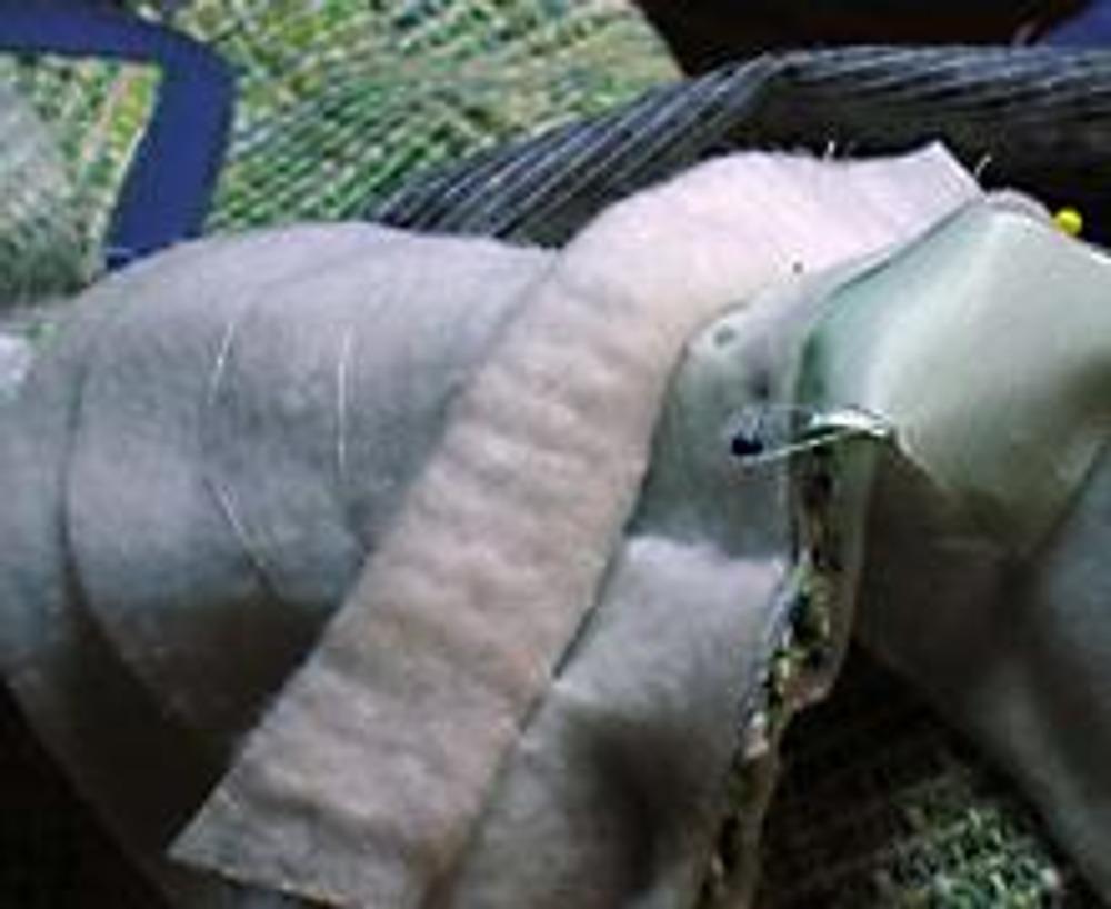 11. Подплечник (в жакетах) иногда (в зависимости от высоты подплечника) вшиваю только по одному слою, утолщенная его часть при этом отвернута. В пальто строчка идет через все слои подплечника. Такой же кусочек подкладочной ткани (3-4 см) вшиваем в нижний участок проймы подкладки. И так же со свободой прикрепляем к нижней части проймы жакета.