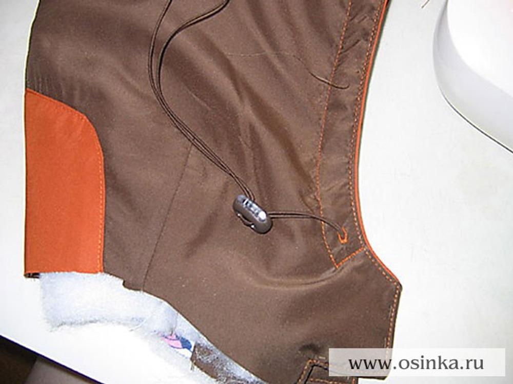 33. Продеть шнур в отверстие так, чтобы его конец заходил за метку на 1 см. Поставить закрепку. Надеть ограничитель и заправить шнур в то же отверстие, чтоб снаружи осталась петля шнура с ограничителем.