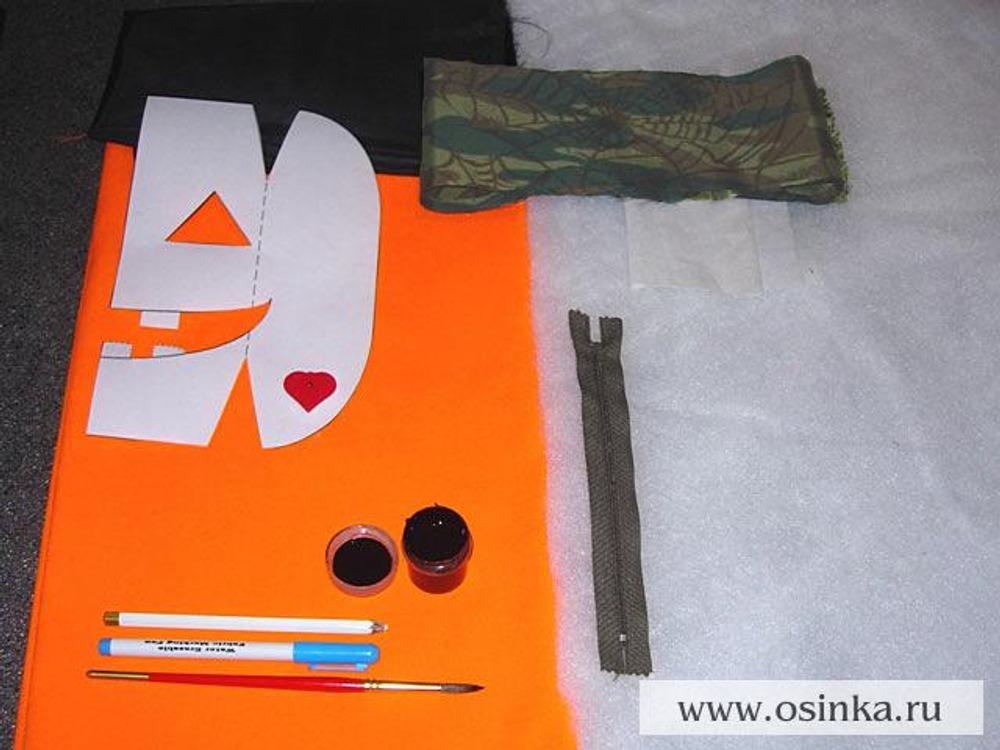01. Для изготовления праздничного аксессуара – сумки в виде тыквы - вам понадобится: - лоскут оранжевой ткани размером 30х80 см; - лоскут подкладочной ткани черного цвета размером 30х100 см; - лоскут плащевой ткани защитной расцветки размером 10х65 см; - черная молния длиной 18 см; - синтепон 0,35 м; - флизелин; - черная акриловая краска для ткани; - 2 кисточки разной толщины; - мел-карандаш; - смывающийся маркер для перевода выкройки; - маркер для ткани перманентный черный; - 2 фонарика в форме сердечка или треугольника размером ок. 3 см; - канцелярские скрепки; - 2 кнопки для застежки.