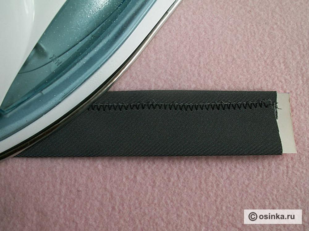 05. Обметанный срез заутюжить поверх, вынуть лекало. Проверить ширину получившейся обтачки.