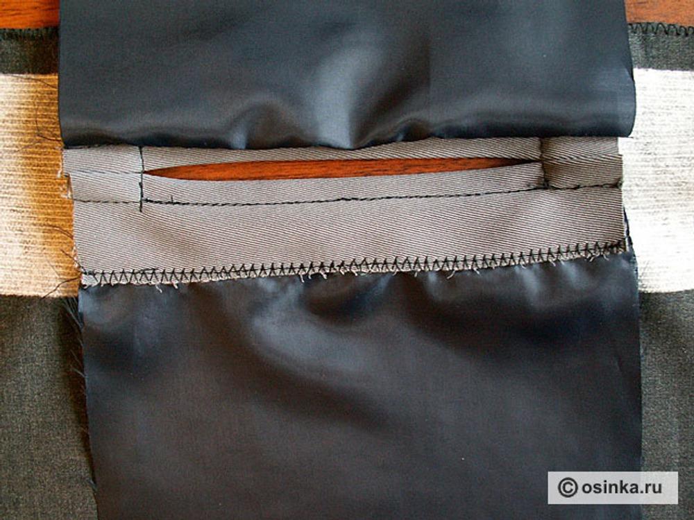21. Отгибаем нижнюю мешковину, оверложенный срез обтачки закрепляем на верхней мешковине, направляя шов посредине оверлочной строчки. Опускаем нижнюю мешковину обратно.