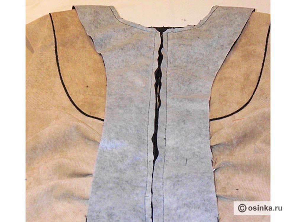 31. Подборта и обтачку складываем с курткой лицевыми сторонами и прикалываем. Подборта притачиваем к нижним срезам полочек, срезам бортов, а обтачку горловины спинки к горловине спинки. Швы срезаем близко к строчке.
