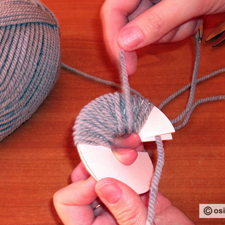 Обмотать вязальной нитью картонное кольцо. Чем лучше заполнен центр, тем плотнее будет помпон.