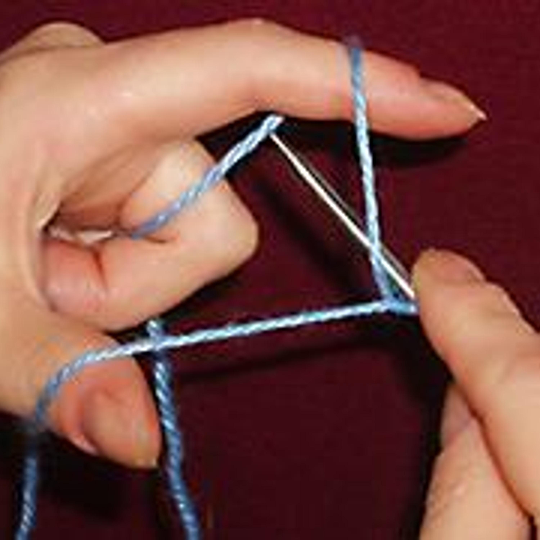 3. Спицу заводим снизу под нить на указательном пальце (со стороны ладони).