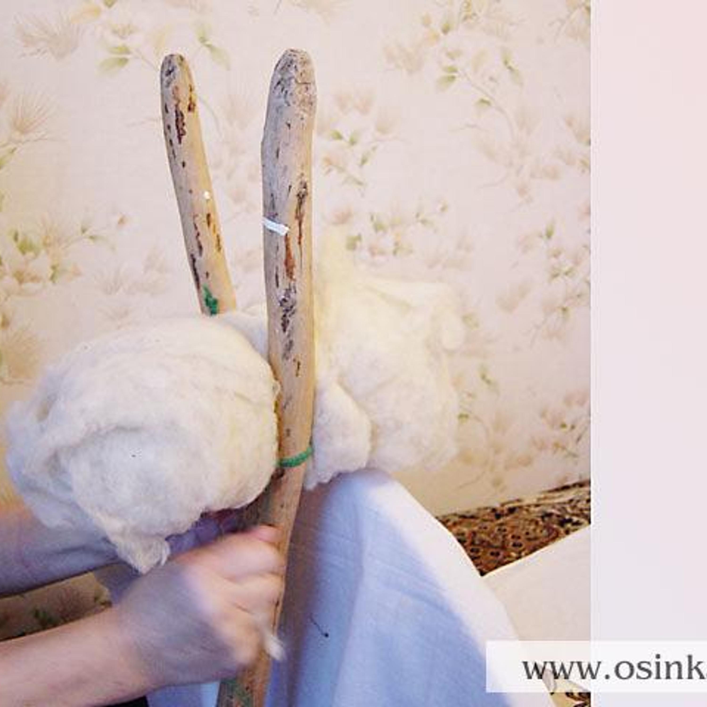 Обработав таким образом 150-200 г , шерсть сворачиваем в кудель, которую крепим - привязываем веревочкой - на стойке прялки (если прялки нет, можно кудель ( чтобы она была примерно на уровне глаз) привязать к любой палке, которую затем укрепить, например, на спинке стула ).
