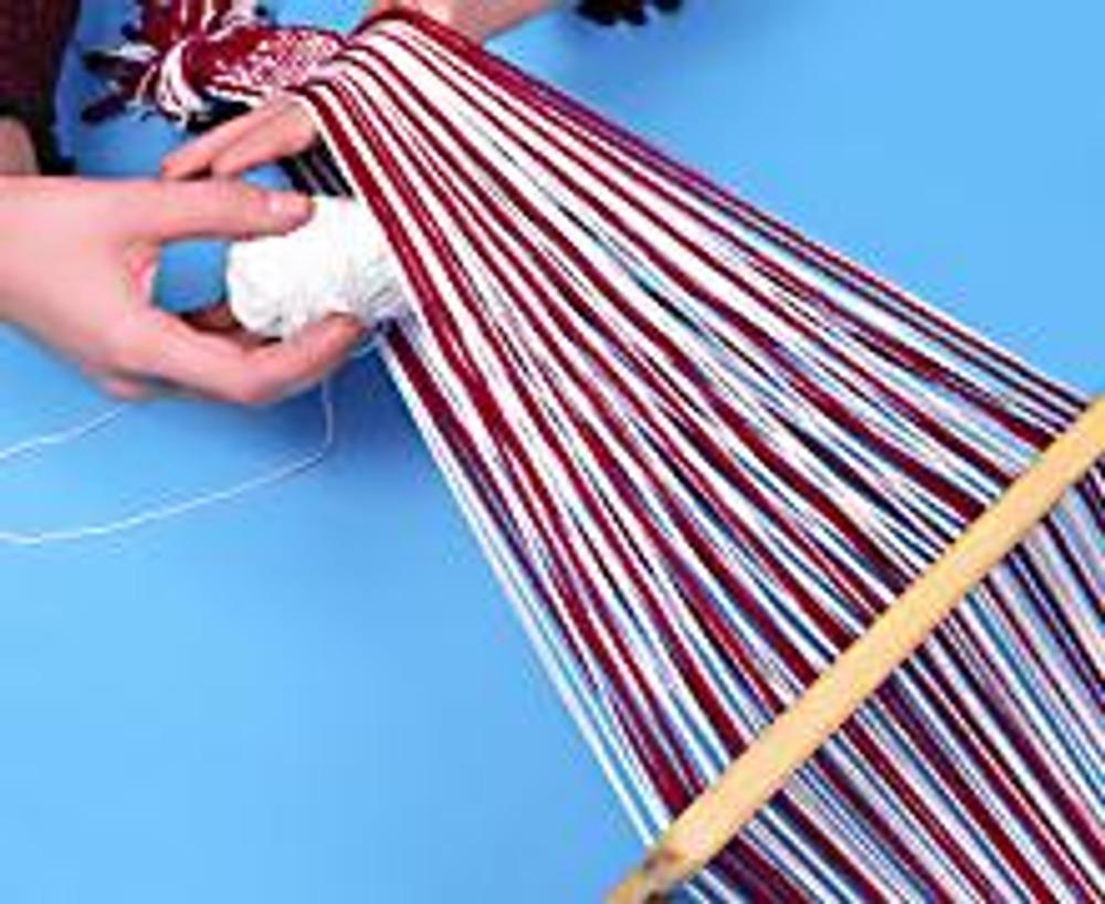 2. Завяжите пучки нитей на концах в узлы и натяните заготовку пояса, закрепив один конец на прочной основе (например, ножке стола) и привязав другой (рабочий) к поясу. Сделайте несколько рядов, чтобы закрепить нити.