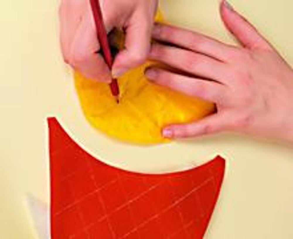 3. Выкройте верх тапочка - 2 детали из оранжевой и желтой подкладочной ткани, 2 -из синтепона. Сложите оранжевую деталь с деталью из синтепона и сделайте стежку, как для подошвы. Так же сложите желтую и нарисуйте карандашом стебли.