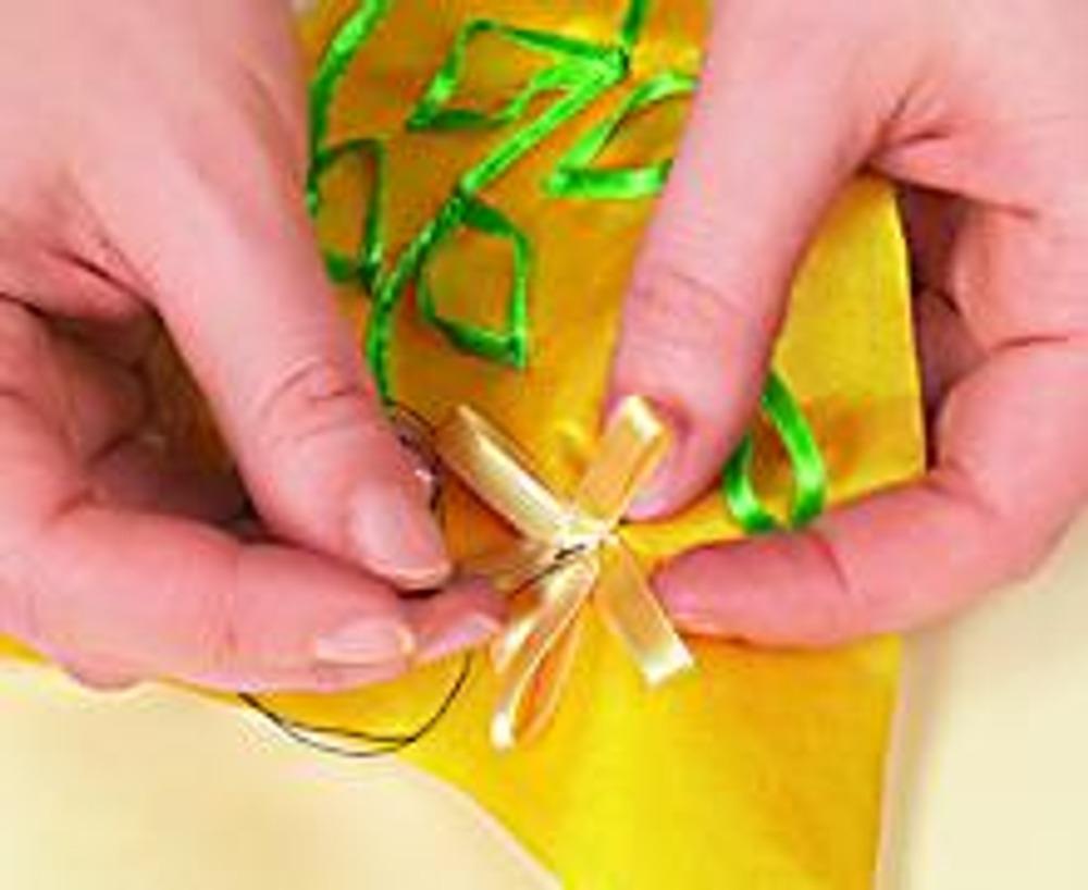 4. Разложите по рисунку зеленую ленту-стебли, одновременно выкладывая листья. Приметайте и пристрочите стебли, закрепите несколькими стежками верхушки листьев.Заложите желтую ленту лепестками, прихватывая ее ниткой к основе. Отстрочите, сделав шов по кругу в середине цветка.