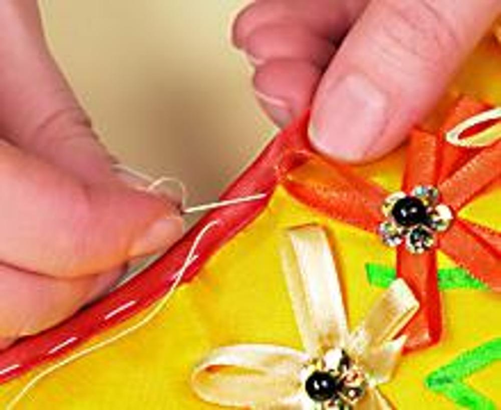 5. Расшейте аппликацию листьями-пайетками и бусинами. Соедините верхнюю и нижнюю части верха тапочка, сметайте и отстрочите по краю. Обработайте косой бейкой внутренний срез верха.