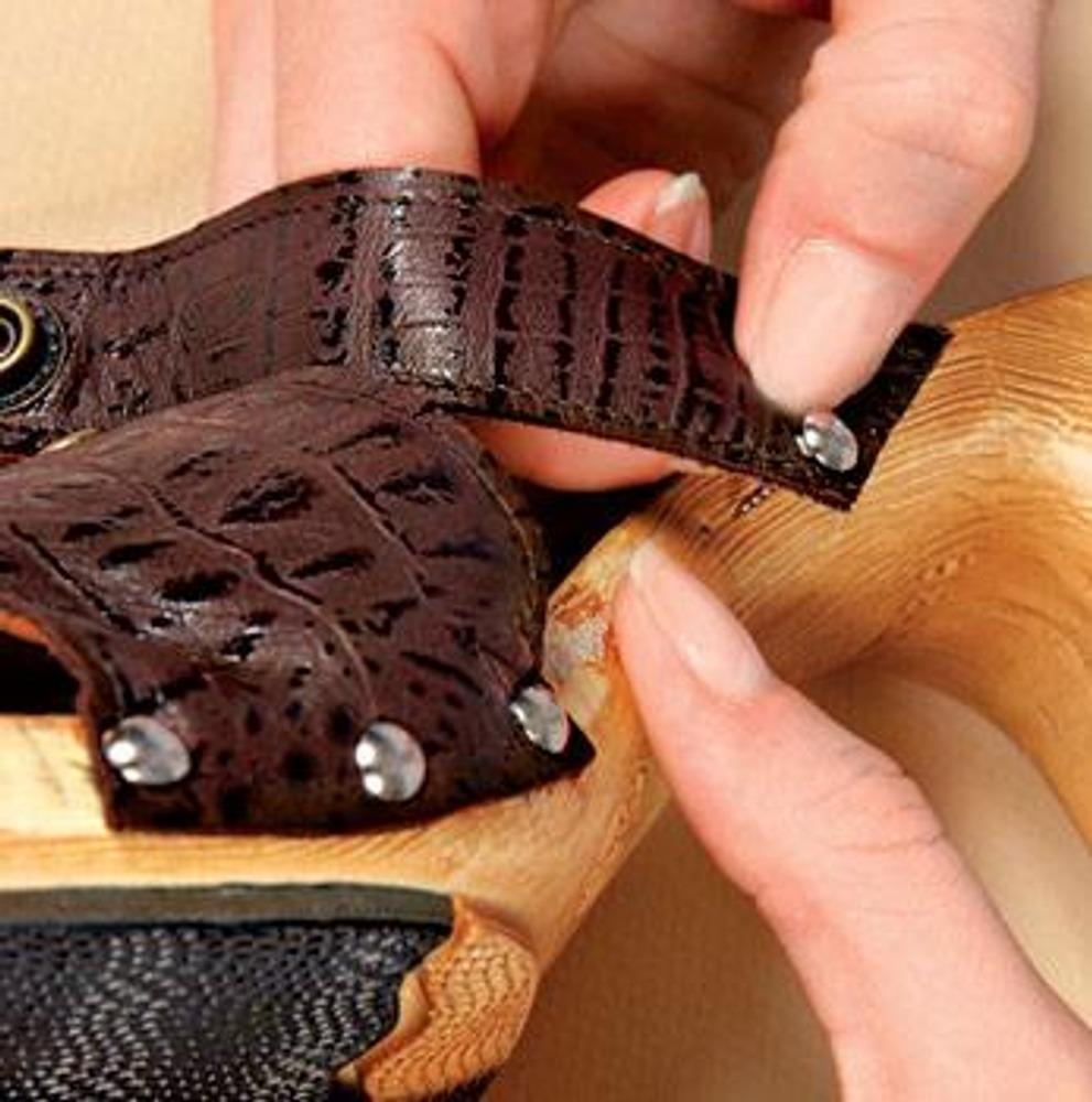2. Поставьте кнопки на отмеченные крестиками места. Лучше делать это в металлоремонте - самостоятельно установленные кнопки плохо держатся. Соедините детали с помощью перемычки. Прибейте подготовленные заготовки к подошве маленькими декоративными гвоздиками.