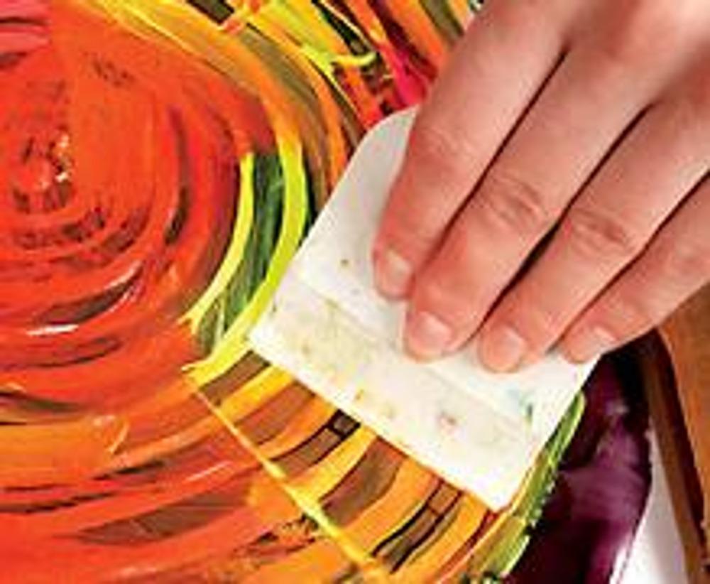 2. Положите поролон на стол, сверху - ткань и раму с трафаретом. Далее вам понадобится помощь - раму нужно достаточно плотно прижать к ткани. Наносите кистью краски на капрон, в некоторых местах смешивая цвета, чтобы получались плавные переходы. Снимите круговыми движениями шпателем излишки краски с трафарета, плотно прижимая его к ткани. Удалите сгустки краски с края шпателя бумагой.