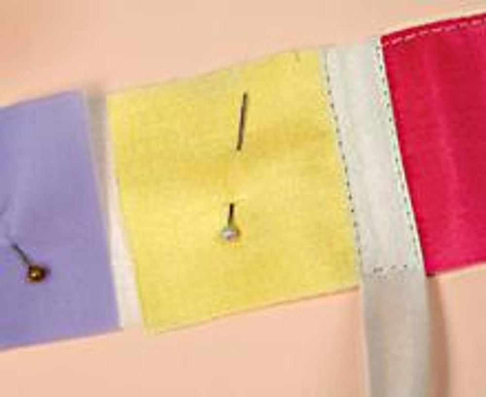 3. Выкройте из цветного шелка квадратики 6 х 6 см. Вырежьте из белой бязи прямоугольник 6 х 52,5 см. Равномерно распределите по бязи квадраты шелка, сохраняя небольшое расстоянии между ними. Приметайте их. Настрочите между квадратами белую косую бейку, так чтобы она перекрывала края шелковых квадратов. Сшейте деталь в кольцо.