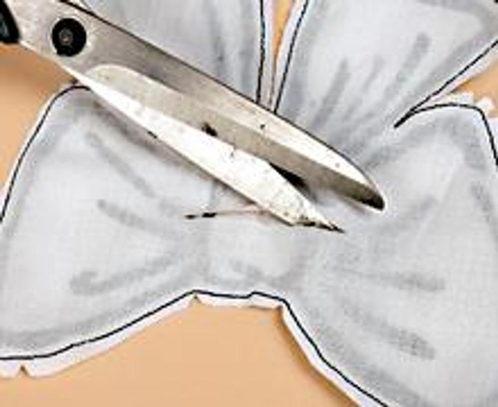 6. С обратной стороны сделайте горизонтальный разрез и выверните через него бант. Выправьте иглой все уголки и разутюжьте. Закройте отверстие потайным швом и отстрочите готовый бант в край.