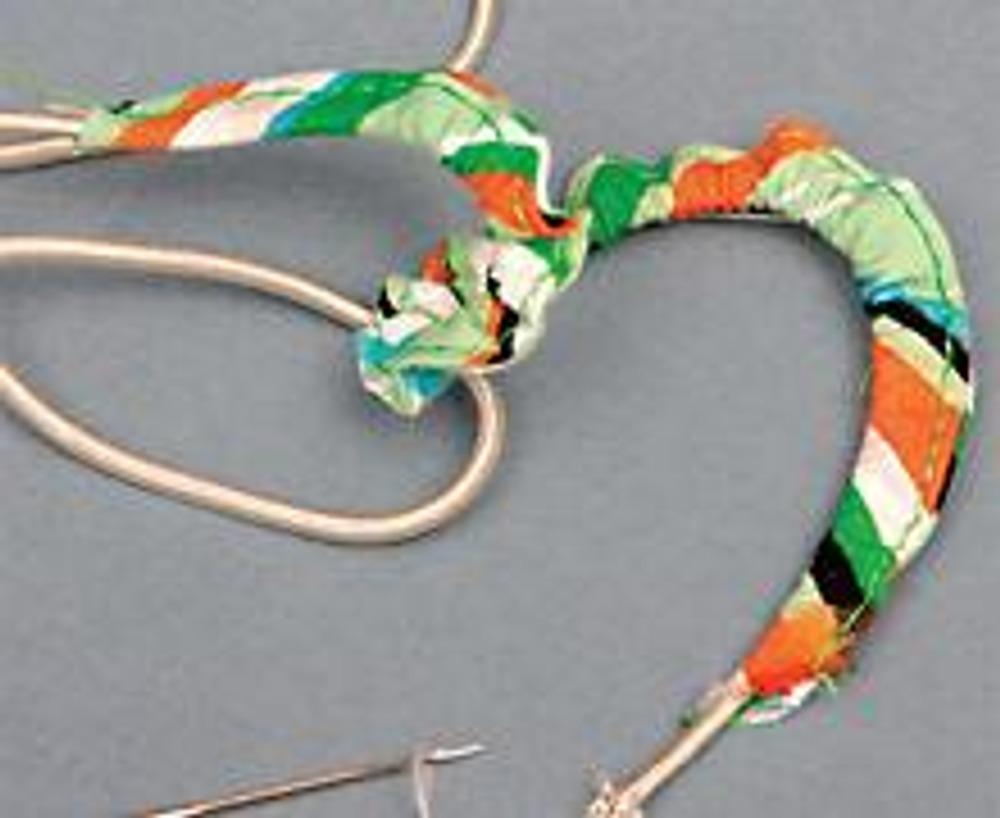 """3. Прикрепите ниткой конец шляпной резинки к концу иглы для швейной машины и проденьте ее сквозь простроченную полоску. Натяните резинку, чтобы присборить ткань. """"Примерьте"""" резинку на пуговицу, чтобы определить размер петли. Отрежьте излишки и закрепите концы."""