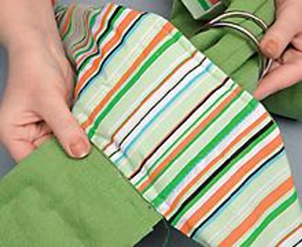 12. Заложите конец основной детали (с вытачкой) в складки, подгоняя ширину края до 11 см. Проденьте этот конец через два кольца и вложите край в оставленную прорезь подушки. Застрочите соединение деталей двойной строчкой.