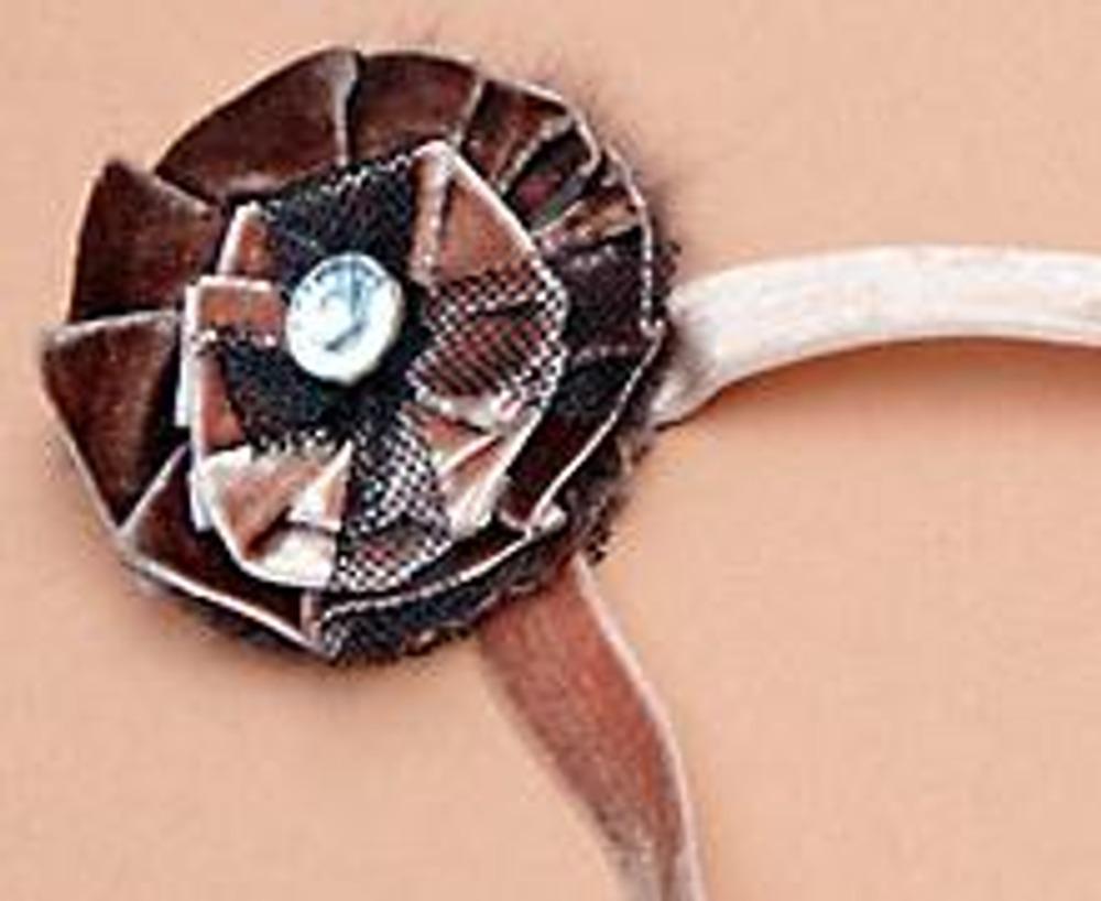 6. Соедините розетки между собой, добавьте небольшой бант из сетки, крупную бусину или пуговицу. Наложите розетки на круг, выкроенный из ободка берета, закрепите. Пришейте булавку.