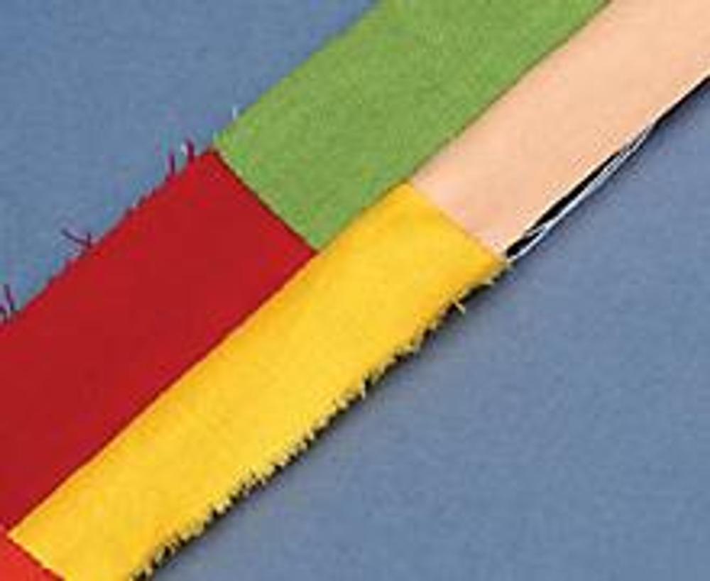 4. Выкройте из хлопчатобумажной ткани прямоугольник таких же размеров, как коврик. Сложите эти две детали лицевыми сторонами, прострочите по краю, оставив отверстие для выворачивания. Выверните, отутюжьте. Проложите по краю фиксирующую строчку.