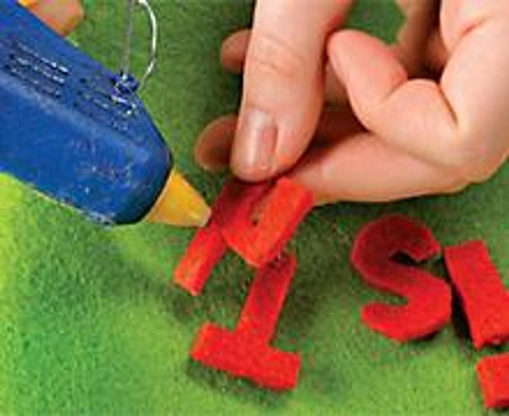 """1. Вырежьте из оранжевого войлока буквы, из которых можно составить фразу """"Где же солнце?"""", и знак вопроса - он должен быть таким, чтобы его верхняя часть огибала круглую ручку сумки. Прикрепите клеевым пистолетом буквы на лицевую сторону сумки. Их также можно настрочить - для этого придется распороть сумку по шву, а затем снова сшить ее."""