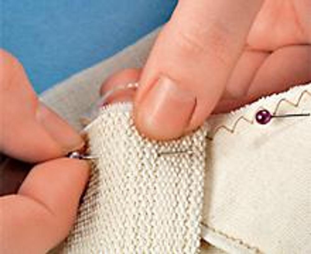 4. Разметьте место для застежки. Вставьте одну из рабочих частей кнопки, пробив ее ножками ткань. Наденьте на ножки фиксирующую пластинку и загните их плоскогубцами. Закрепите на подкладке вторую рабочую часть кнопки. Пришейте подкладку к основе сумки, сложив обе детали и проложив фиксирующую строчку. Выверните сумку через оставленное в подкладке отверстие и зашейте его потайным швом.