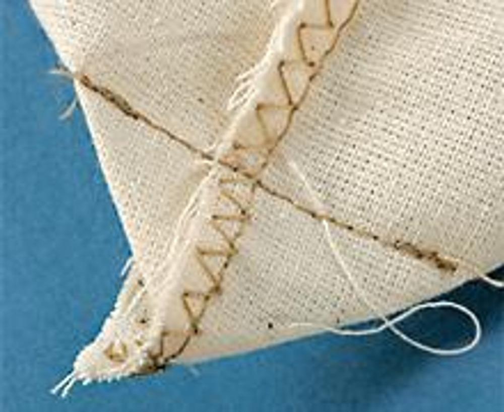 """1. Сшейте основу сумки, выкроив из светлого, более плотного хлопка 2 одинаковых прямоугольника. Сложите их лицом к лицу и стачайте по трем сторонам. Обработайте срезы швом """"зигзаг"""". Застрочите уголки, формируя дно."""