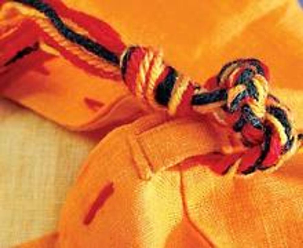 4. Разрежьте нити пряжи оранжево-желтых оттенков на части длиной около 1,7 м. Добавьте 2-3 черные нити. Сложите их, завяжите узел в 15 см от конца пучка и сплетите косичку толщиной 1 см. Привяжите концы косички-ручки к шлевкам.
