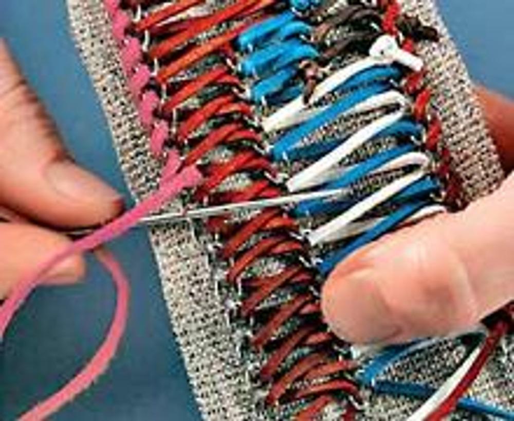 6. Декорируйте края пояса шнуром контрастного с основой цвета. Обшейте им внешние стороны крайних цепочек.