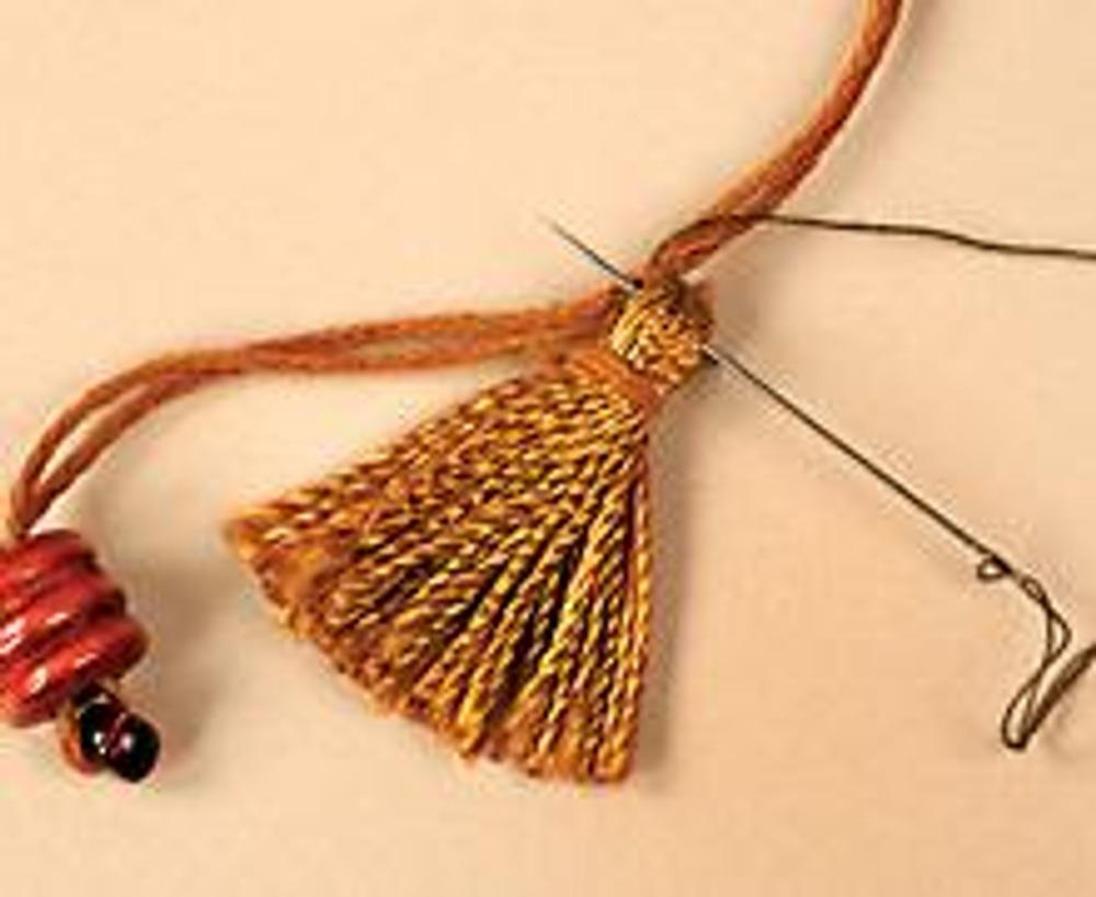 1. Нанижите на нить мулине (сложенную в 6 раз) бисер и деревянные бусины разной формы, пришивая между ними кисточки. Чтобы кисть крепко держалась на нити, сделайте несколько стежков вспомогательной нитью.
