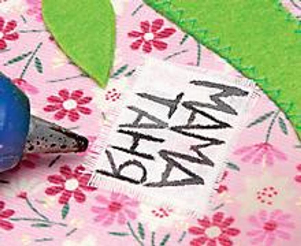 2. Настрочите дерево на деталь из вельвета. Используя клеевой пистолет, наклейте листья. Изготовьте подписи-таблички из хлопчатобумажной ткани. Для этого напишите на ткани акриловой краской имена членов семьи, дайте краске высохнуть, а затем прогладьте надписи горячим утюгом через кальку. Наклейте таблички на основную ткань возле веток дерева.