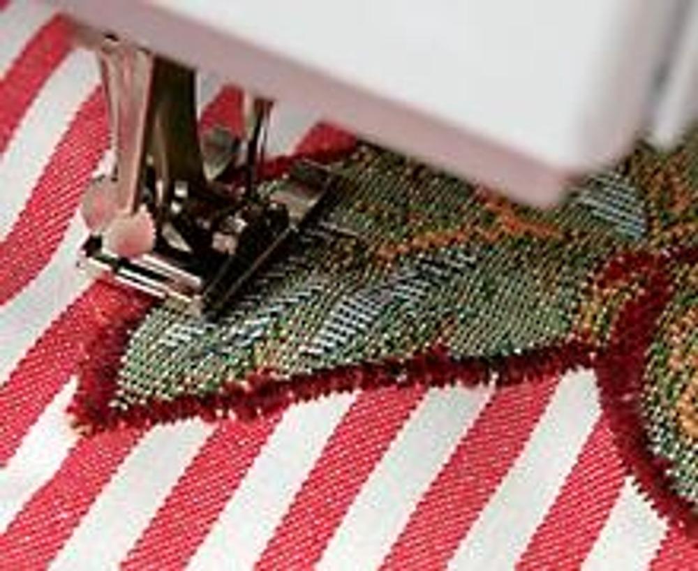 """5. Настрочите аппликацию по краю на ткань наволочки швом """"зигзаг"""", подобрав нитки под цвет покрывала. Установите ширину строчки 3,5-4 мм, длину стежка - 0,3-0,5 мм. К основанию букета пришейте ленту. Сложите ее концы и приколите к ткани. Обработайте намеченные петли."""