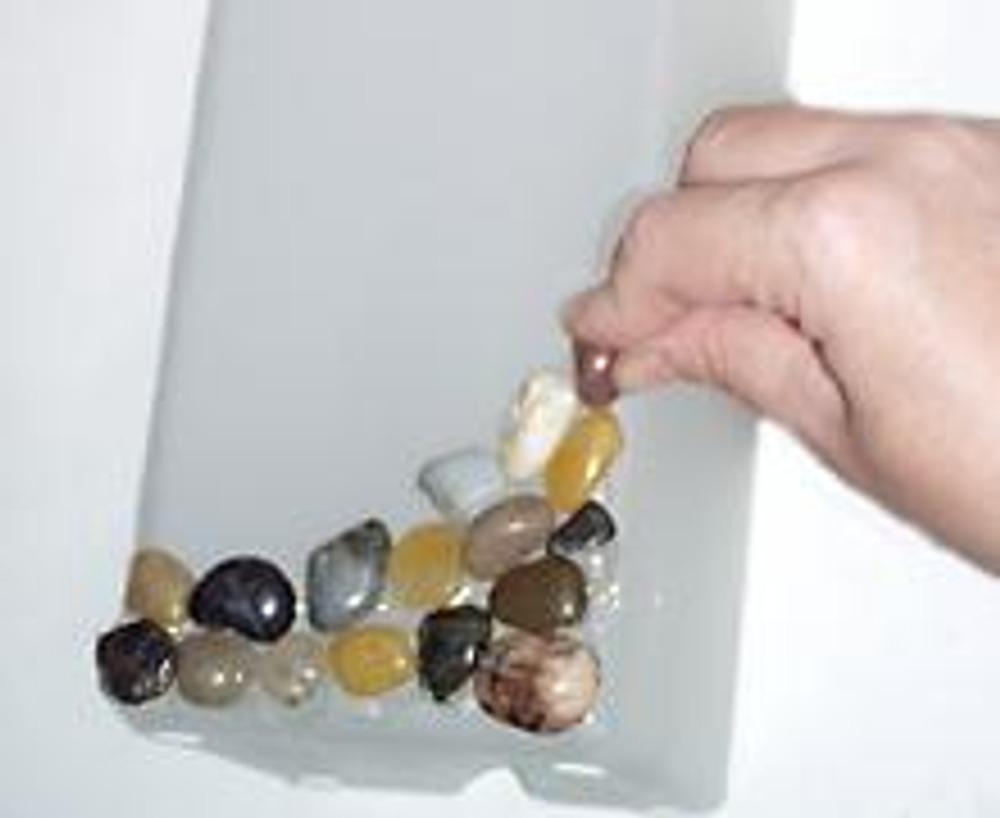 1. На нижнюю часть лампы приклейте суперклеем или термо-клеем камушки так, чтобы они постепенно поднимались вверх. Не жалейте клея, галька должна как бы утопать в клею.