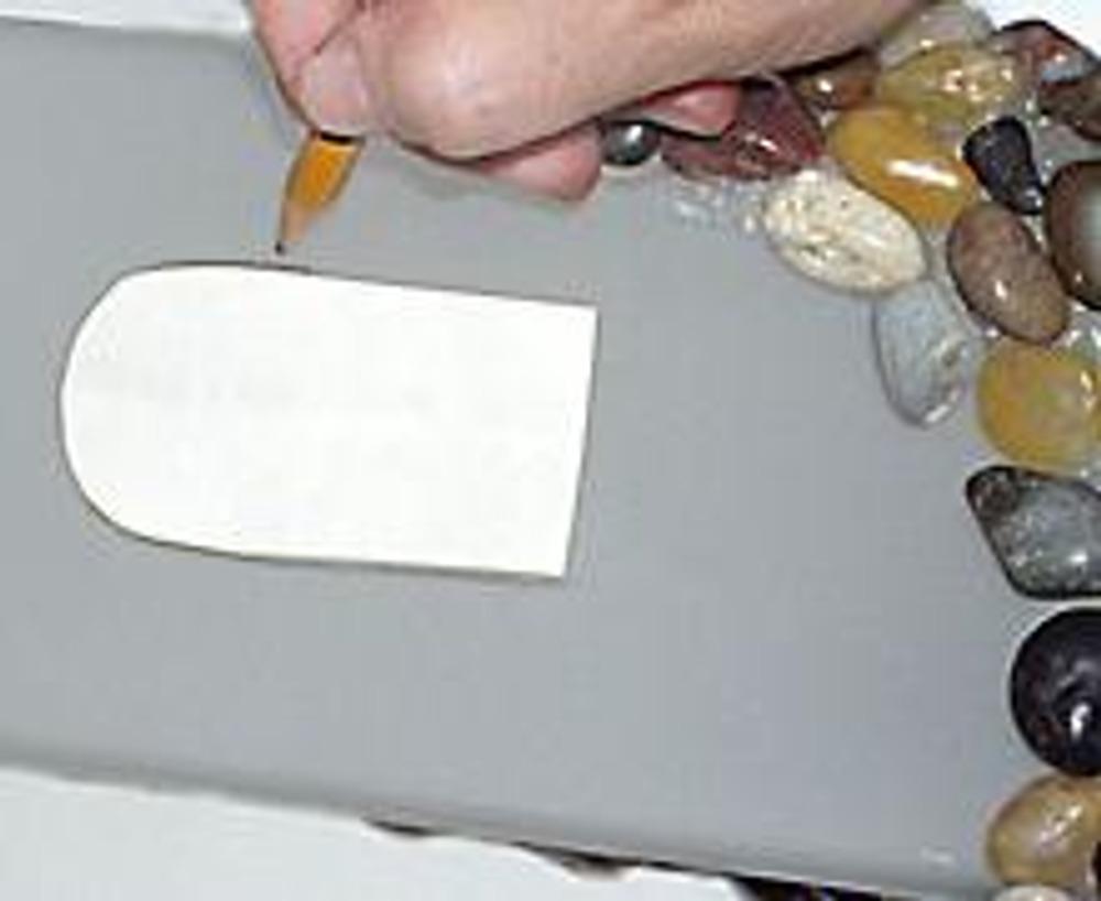 2. Из бумаги вырежьте арочный трафарет окна. Приложив его на каждую сторону лампы, обведите карандашом