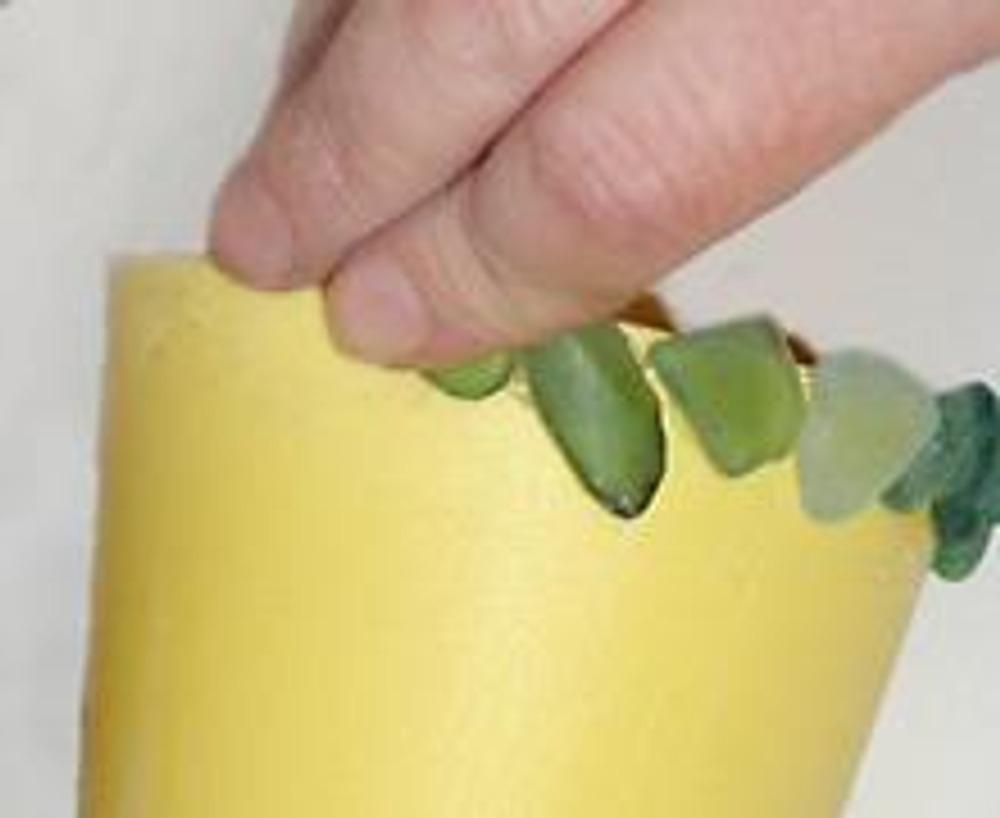 4. Затем, прикрепите маленькие ракушки. Нанесите суперклей на небольшую поверхность стаканчика и распределите ракушки, так чтобы они плотно прилегали друг к другу. Клея кладите довольно много, неровная поверхность ракушек как бы утопает в нем.
