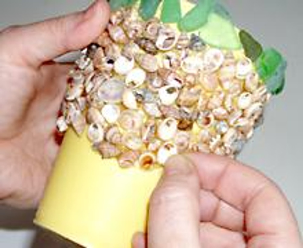 5. Прижимайте пальцам декор до полного высыхания клея. Особенно будьте аккуратны, приклеивая ракушки у основания донышка. Следите за тем, что бы они не выходили за край, иначе стаканчик будет стоять не ровно.