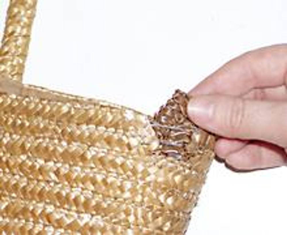 1. Небольшие отрезки тесьмы разместите в протертом месте, между подкладкой и соломкой сумки.