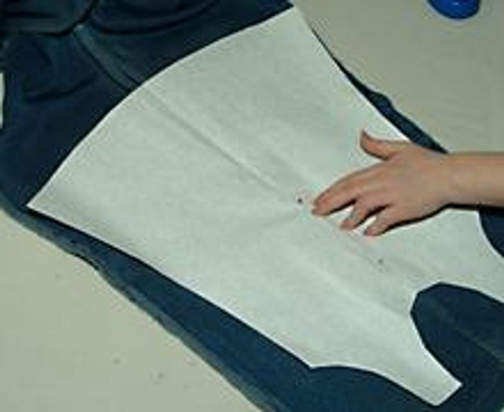 3. Наложите выкройку детского сарафана так, чтобы его середина совпадала с оставленным швом на джинсах.