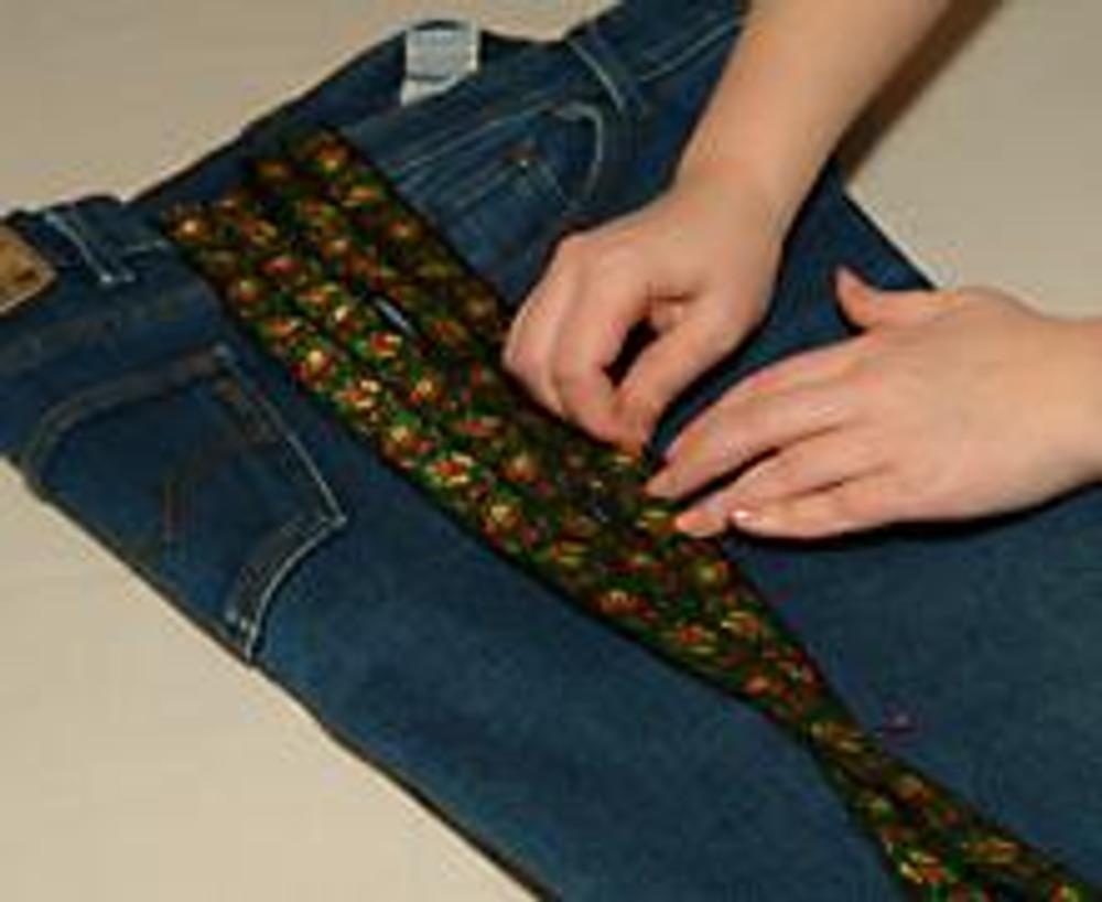 5. Готовую конструкцию из тесьмы накладываем на распоротый боковой шов. Приятный побочный эффект - джинсы приобретают модный клеш внизу!