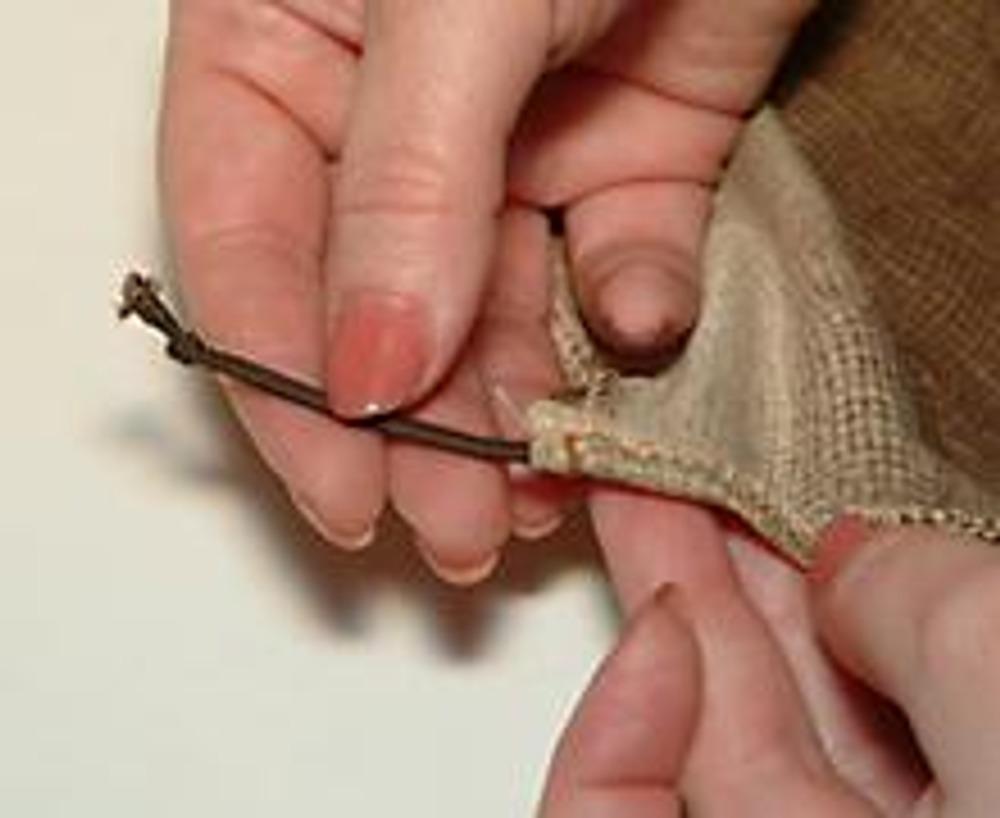 6. На оставшемся отрезке резинки (ок. 9 см) завязать на концах узелки и вложить узелками в припуск по низу.