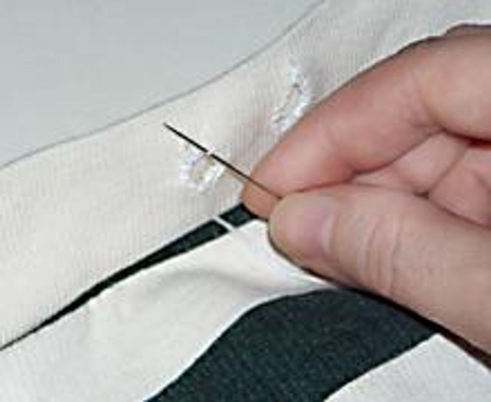 8. По середине верхней части сумки (в трикотажной резинке), прорежьте две небольшие дырочки. Толстой ниткой обработайте отверстия петельчатым швом. Проденьте в кулиску шнур и скрепите его ограничителем.