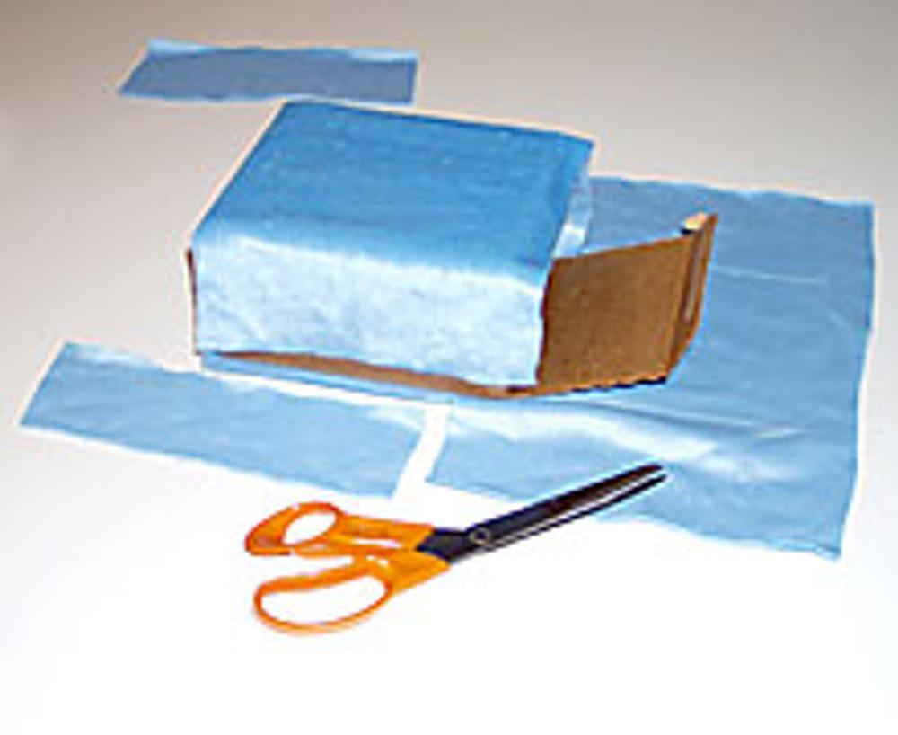 2. Положив коробку на мех или на бумагу, сделайте выкройку, для того чтобы обтянуть коробку и сшить подкладку. Проверьте лекала, обернув ими коробочку.