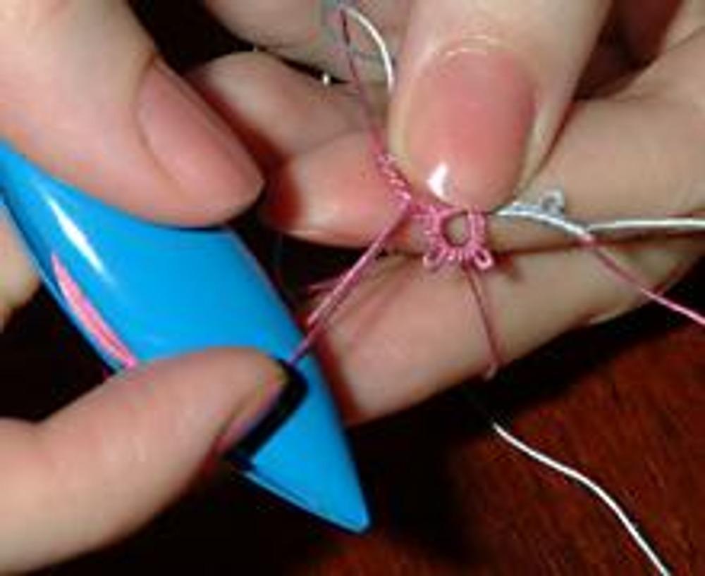 25. Вводим челнок в вытянутую петлю, нить от челнока держим натянутой.