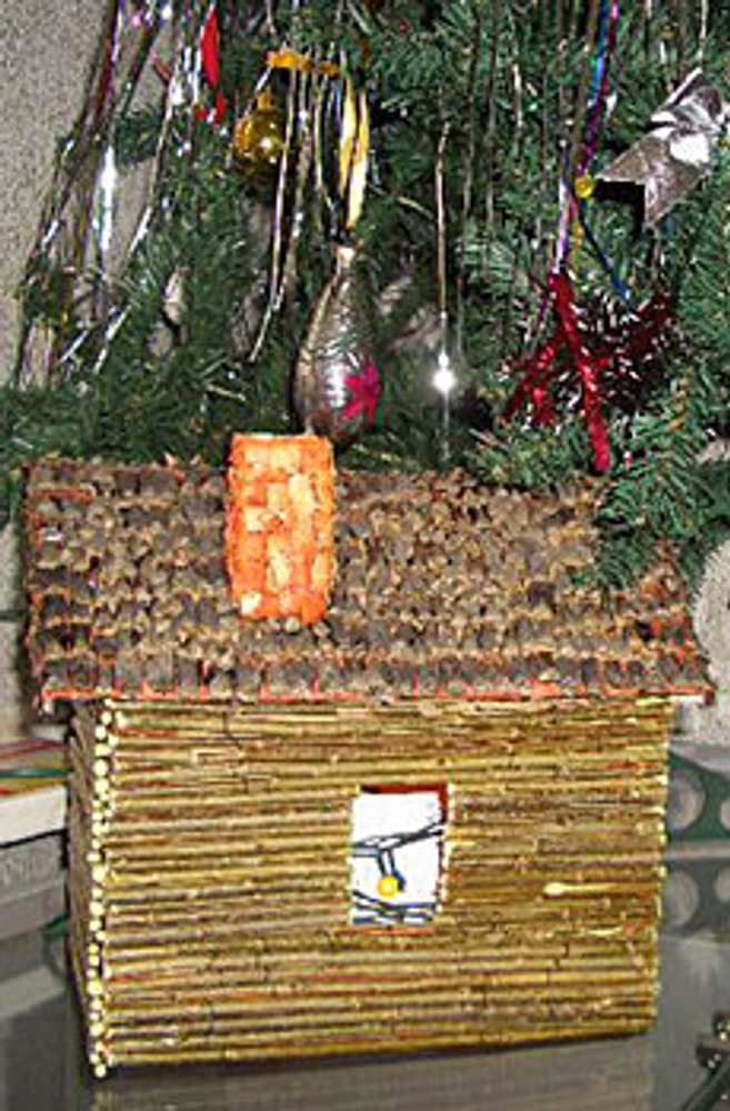 Домик сделан из картона, стены обшиты прутиками ивы, на крышу наклеены кусочки разобранных шишек, а труба покрыта панцирем вареного рака. Через дверь или окошко протягиваются в домик герлянды для того чтобы он светился из нутри.