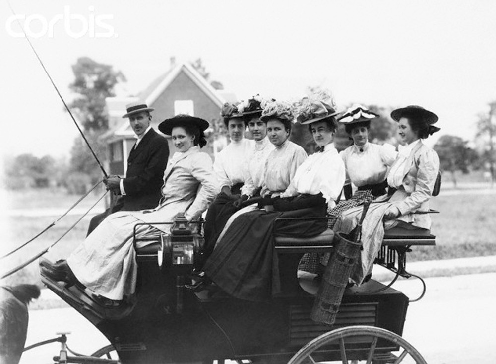 Women seated in a carriage taking a ride with a man driving the coach.  1890s-1900s