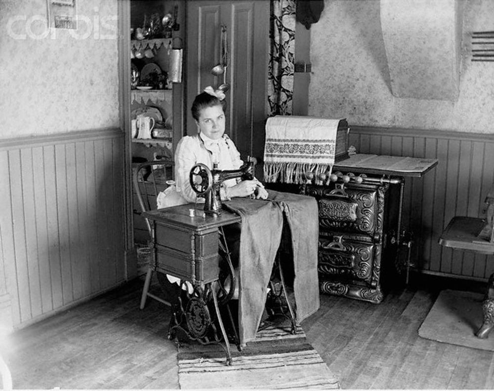 Augusta Munson sews a pair of jeans on an of old Singer sewing machine, 1905