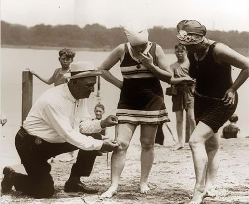 Фото. Измерение длинны женского купальника. Если он окажется короче, женщина покинет пляж и будет оштрафована. 1920-е гг.